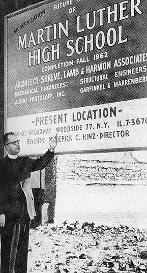 Black and white picture from the early 1960s shows priest standing in front a sign announcing new Martin Luther School building project.