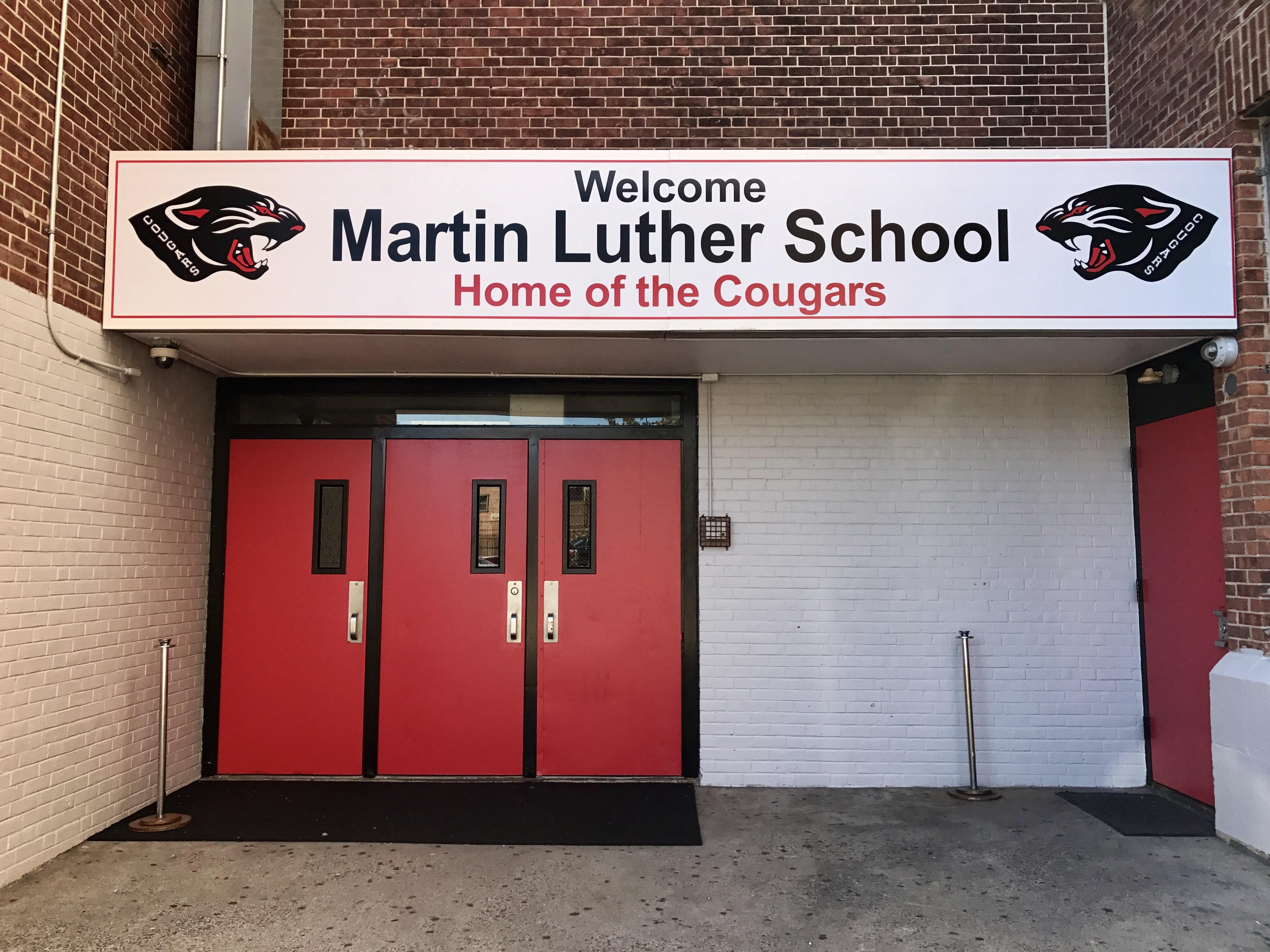 Front facade of Martin Luther School; name banner hangs above three red metal doors.