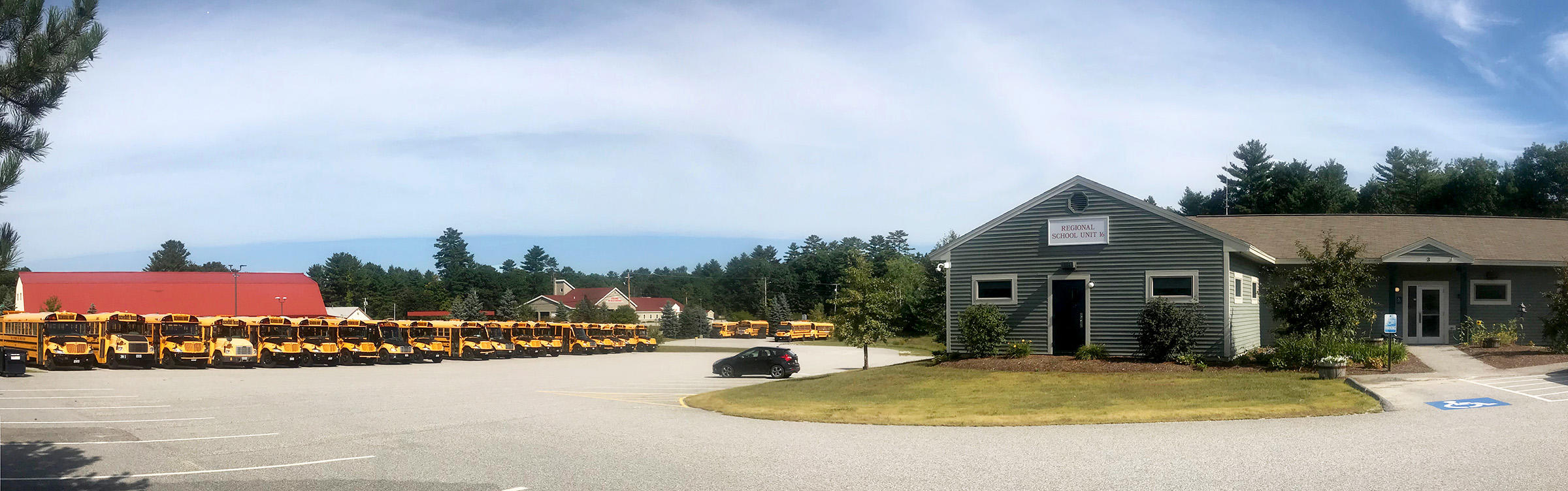 Photo of RSU 16's Central Office Building with school buses lined up in the bus area.