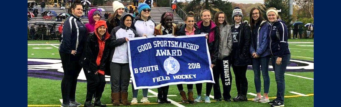 Photo of the girls field hockey team holding the 2018 Good Sportsmanship Award flag.