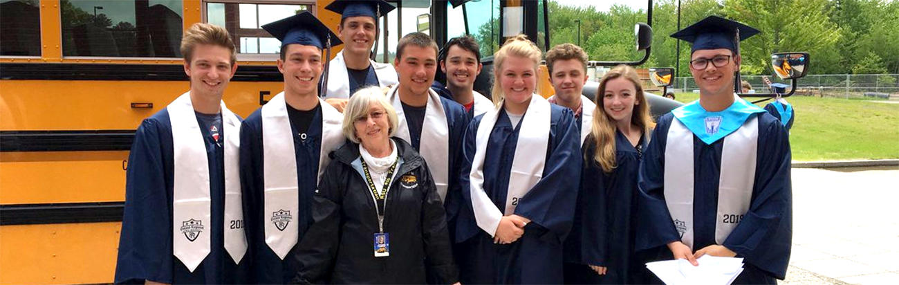 Photo of seniors in their caps and gowns, saying goodbye to their 'whole school career' bus driver, Sue Harris!