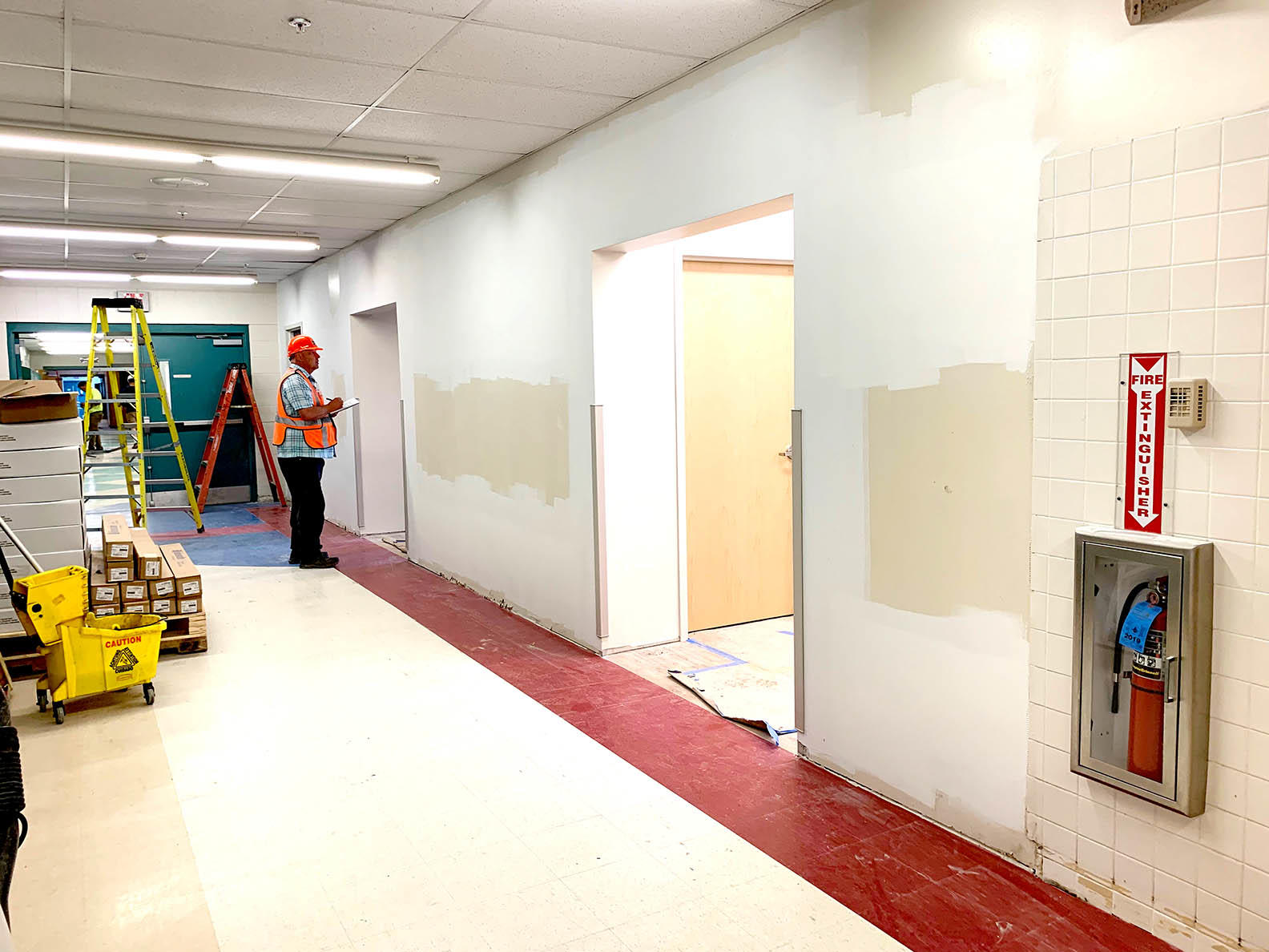 Photo of construction in hall looking into offices.