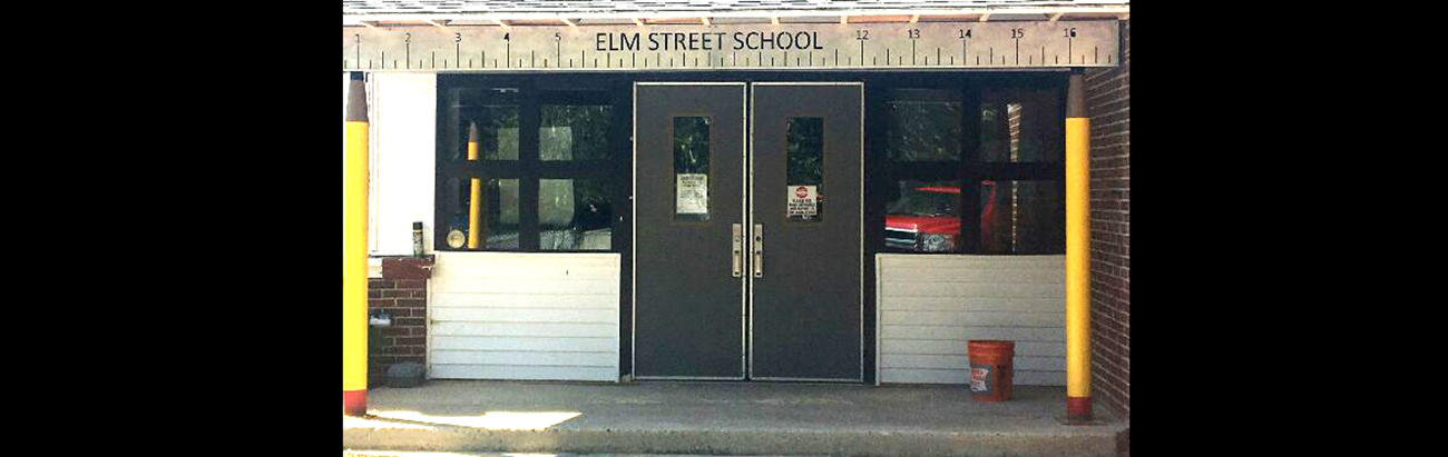 A photo of the front of Elm Street School which shows the pencil and ruler used in the design, donated by Caleb Bickford