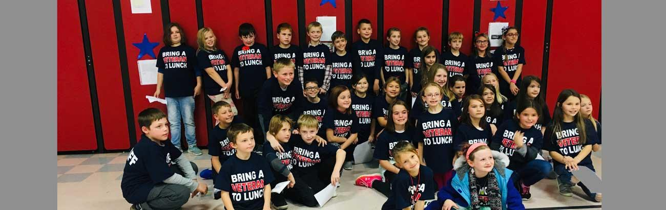 Photo of group of students involved with 'Bring a Veteran to Lunch'. They are all wearing T-Shirts with 'Bring a Veteran to Lunch' printed on them.