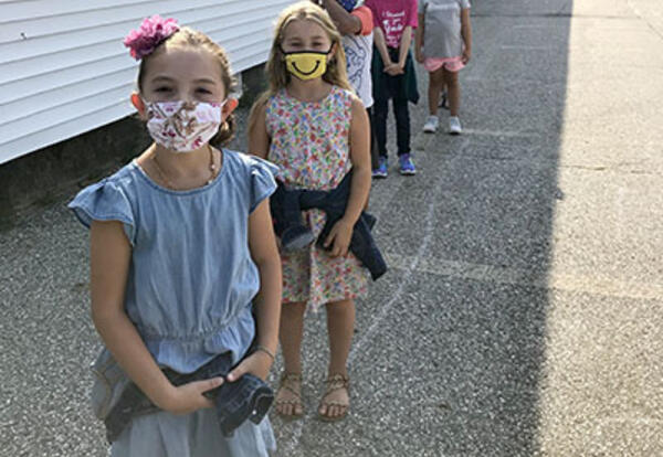 ESS Students Together outside the school wearing masks.