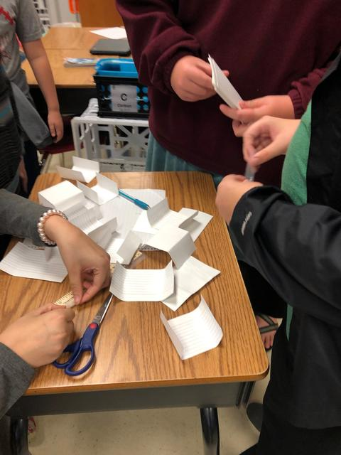 Closeup of student hands that are working on paper tower project