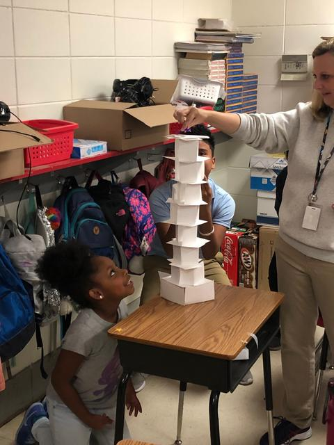 Teacher places coin on tower while female student looks up expectantly