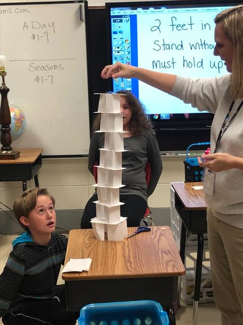 Teacher places paper on top of tower while student looks on worriedly
