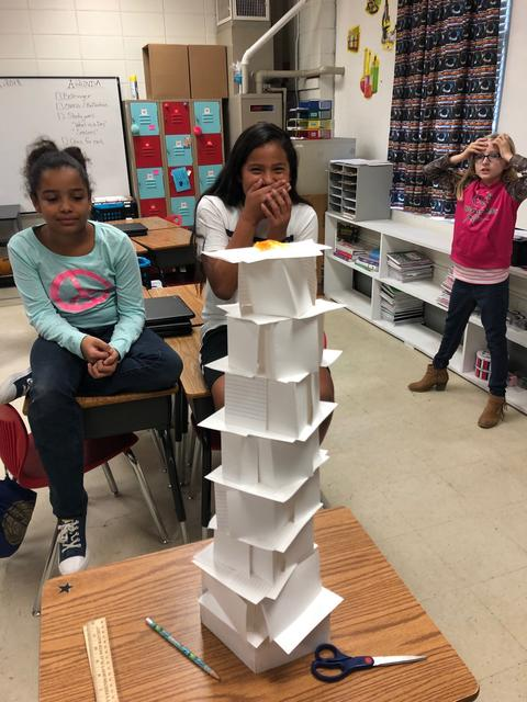 Two students stand behind their paper tower creation; one has hands over her mouth.