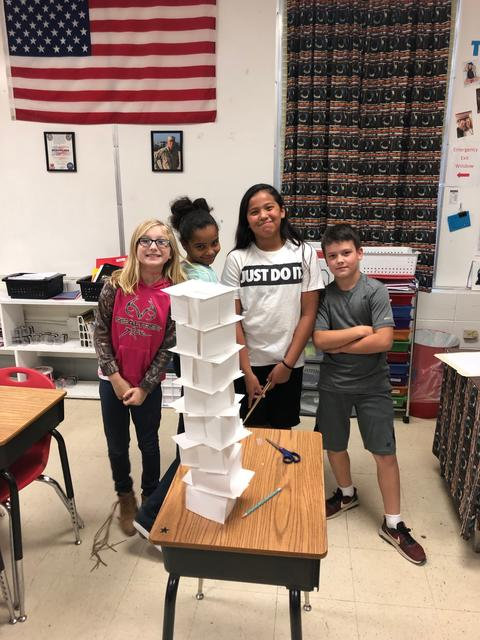 Three young students stand next to tower made of medium-size paper cubes