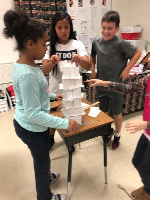 Students in action, placing paper tiles on tower