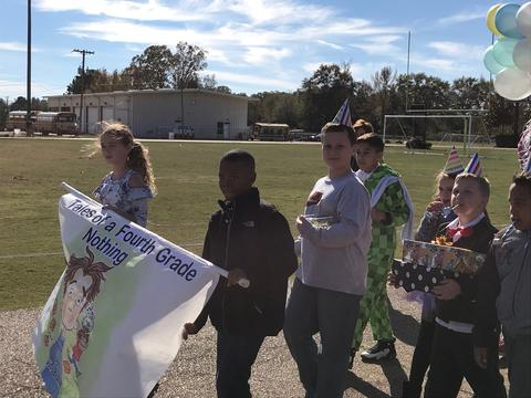 Students walking with book banner