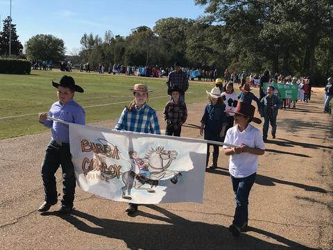 Students with cowboy hats walking with book banner