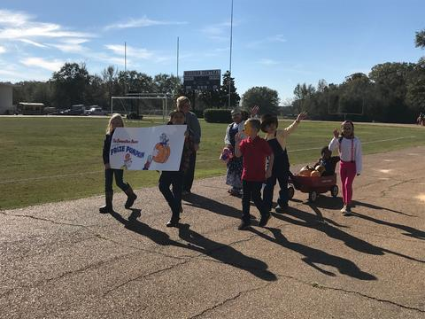"""Students walking with """"Prized Pumpkin"""" book banner"""