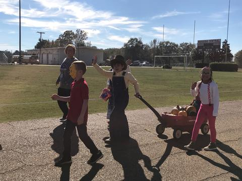 Students in costume pulling a red wagon