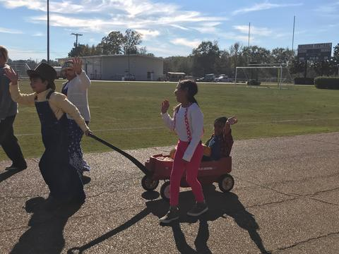 Students pulling and walking next to red wagon