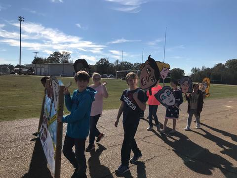 Students walking with big cardboard face signs