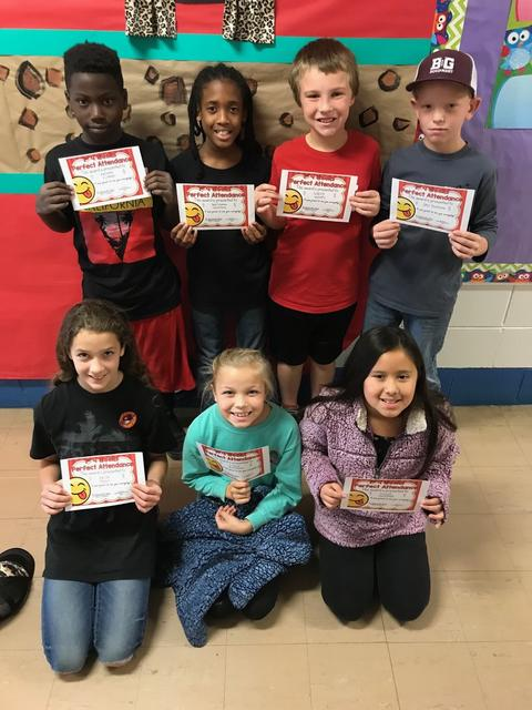 Seven students pose with certificates