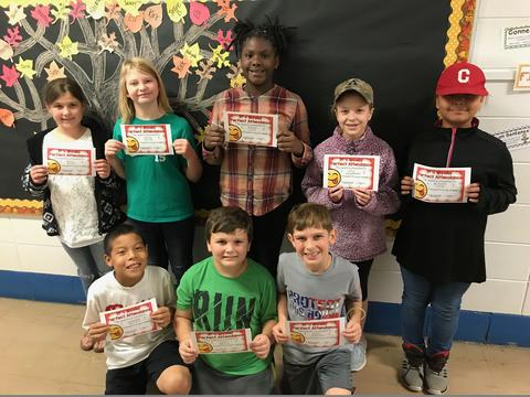 Eight students pose with certificates
