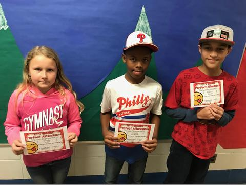 Three students pose with certificates