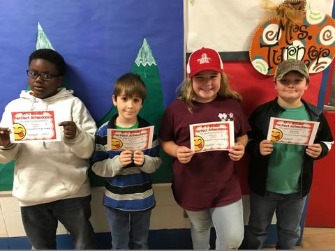 Four with students (two with hats) pose with certificates