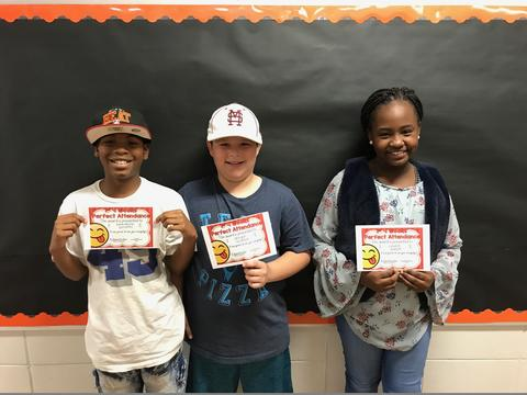 Three students pose with certificates against a black bulletin board