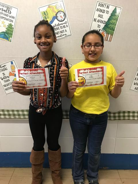 Two students have thumbs up while holding certificates