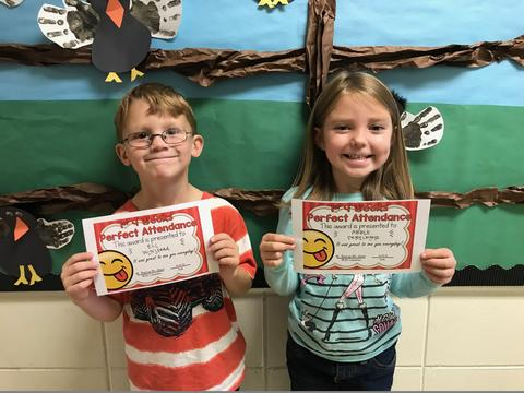 Two students holding certificates and standing against colorful bulletin board