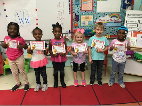 Six students standing in a row, holding certificates