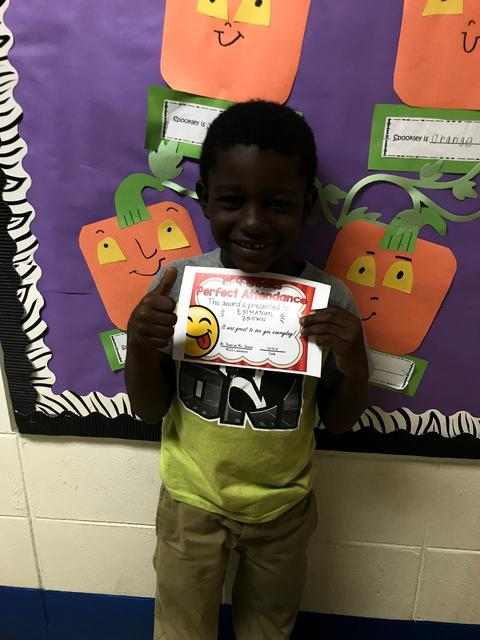Student holding certificate while standing next to pumpkins on bulletin board