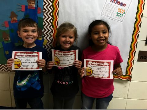 three students smiling and holding certificates