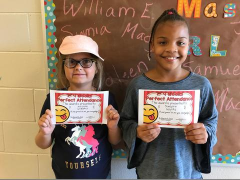 Two female students hold certificates and smile