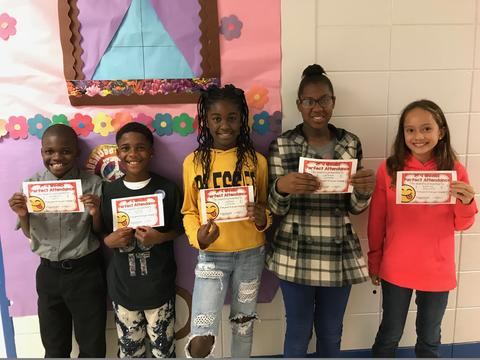 Five students pose against bulletin board with certificates