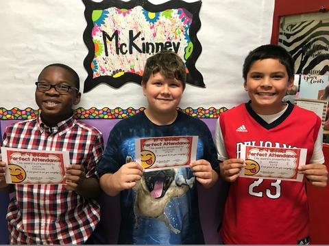 Three male students smile and hold certificates