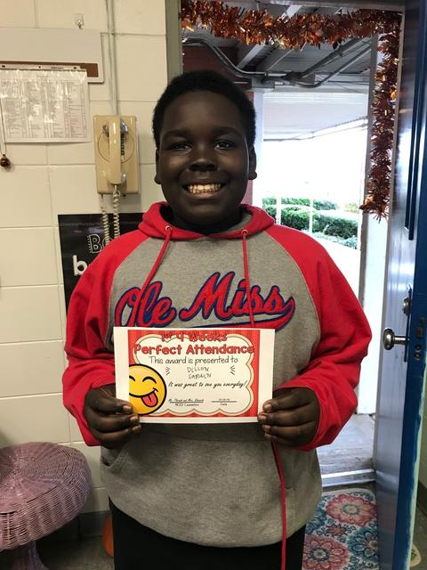 Male in Ole Miss sweatshirt poses with certificate