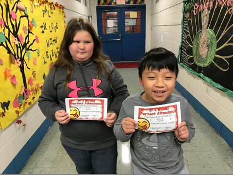 Two students pose in hall with certificates