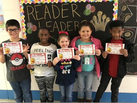 """Five students pose against """"Readers are Leaders"""" bulletin board"""