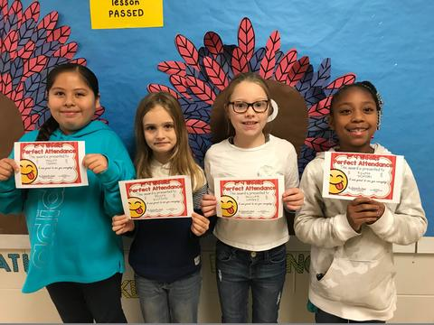 Four students pose against Thanksgiving bulletin board