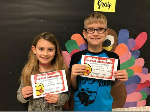Two students pose against turkey bulletin board