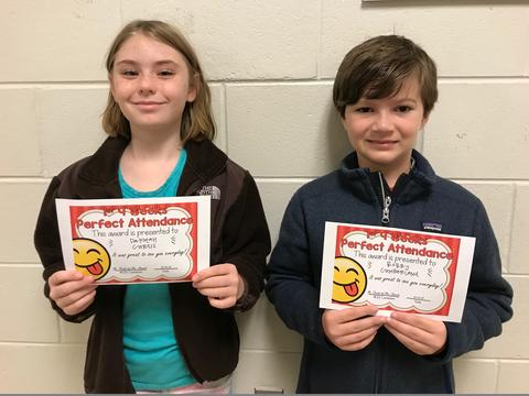 Two students pose against wall with certificates