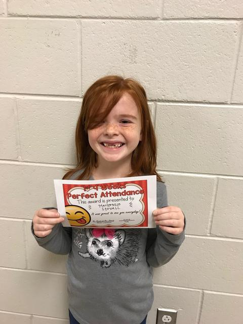 Red-headed female student posing and smiling with certificate