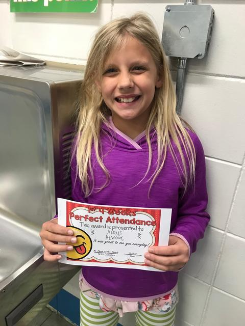 Blonde student smiles with certificate