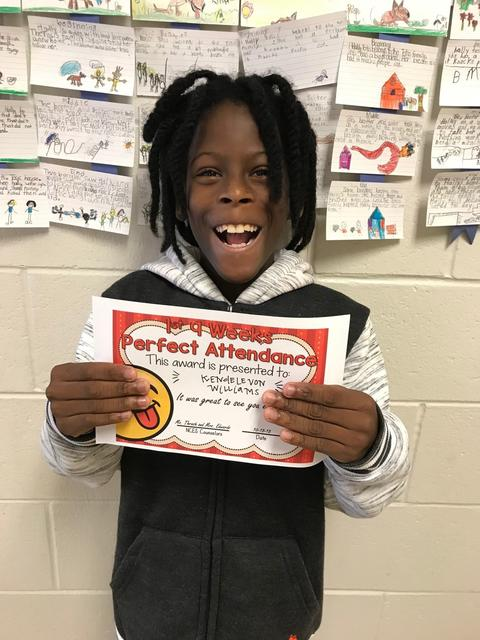 Student with black braids and big smile holds certificate