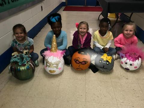 Smiling young students and decorated pumpkins: witch, unicorn, bat, and cat