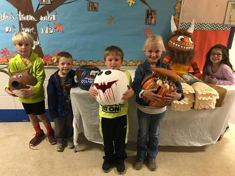 Students with pumpkins: Scooby Doo, goblin, and a pumpkin filled with stuffed kittens