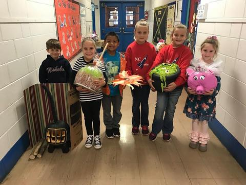 Students with pumpkins decorated as a caramel apple, cauldron, and a pig
