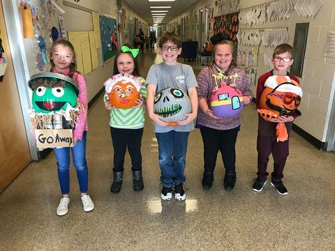 Students with pumpkins decorated as Oscar the Grouch, granny, a skeleton, a house, and a pumpkin creature