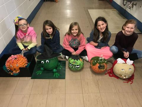 Students with pumpkins decorated as a porcupine, frog witch, Frankenstein, gnome house, and redheaded doll
