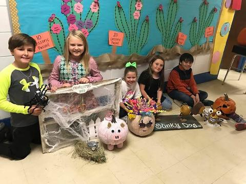 Students with pumpkins decorated as Charlotte the pig, confetti head, and a bug