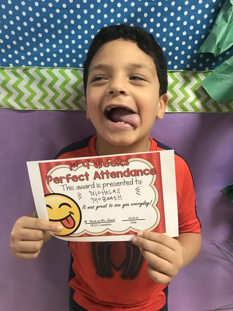 Student goofs, sticks tongue out, while posing with certificate